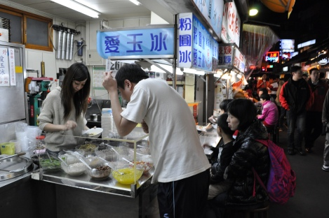 man choosing the ingredients for a sweet treat/shida night market, taipei/dec 2012